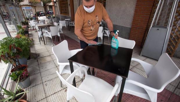 ep un camarero limpia una de las mesas de su bar
