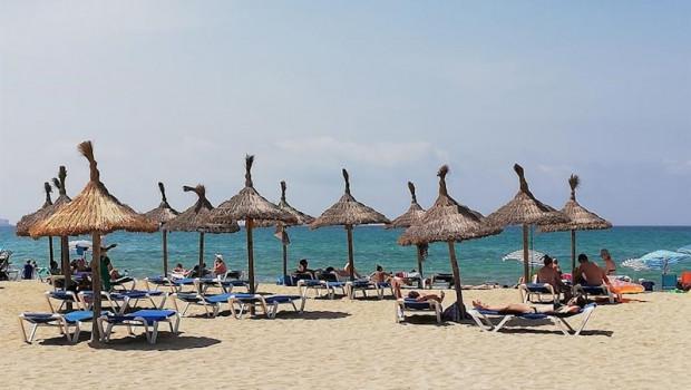 ep turistas en hamacas bajo las sombrillas de la playa de palma